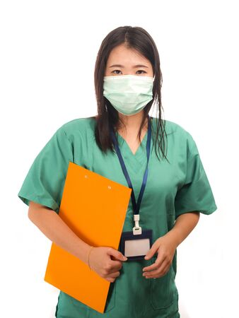 Photo pour young beautiful Asian Korean medicine doctor woman or hospital nurse holding clipboard  in scrubs using protective medical face mask in prevention against virus infection isolated on white background - image libre de droit