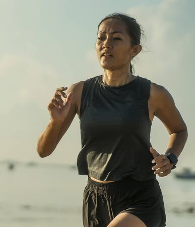 Photo pour outdoors fitness portrait of young attractive and athletic Asian Indonesian woman in her 40s running on the beach doing intervals workout in athlete training concept and healthy lifestyle - image libre de droit
