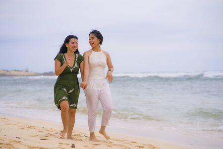 Photo pour young beautiful and happy couple of attractive Asian Korean women walking together relaxed at the beach enjoying holidays having fun feeling free and joyful  in girls friendship concept - image libre de droit