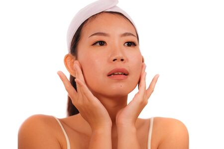 Photo for isolated portrait young beautiful and happy Asian Korean woman applying skincare wrinkle prevention treatment or aging beauty product on her face in makeup cosmetic and healthy lifestyle - Royalty Free Image
