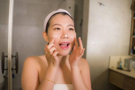 Photo pour home lifestyle portrait of young happy and beautiful Asian Korean woman at bathroom mirror applying skin care moisturizer and anti-aging product in beauty and skincare concept - image libre de droit