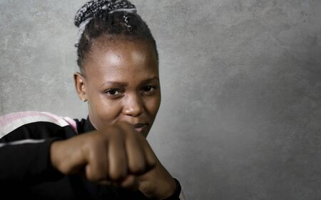 Photo pour isolated portrait of young cool and confident black afro  woman in fighting stance looking defiant rising her fist throwing punch in badass attitude isolated on grunge background - image libre de droit