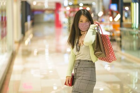 Photo pour New normal habits - young attractive and happy Asian Korean woman at shopping mall happy and excited enjoying sale in beauty fashion store carrying shopping bags - image libre de droit