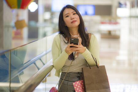 Photo pour young beautiful Asian woman shopping at modern mall - happy and attractive Korean girl holding shopping bags using mobile phone enjoying sale buying at beauty fashion store - image libre de droit