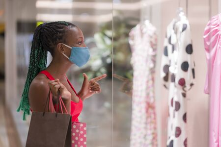 Photo pour young African American woman at shopping mall in new normal after covid-19 - happy and beautiful black girl in face mask holding shopping bags enjoying at beauty fashion store - image libre de droit
