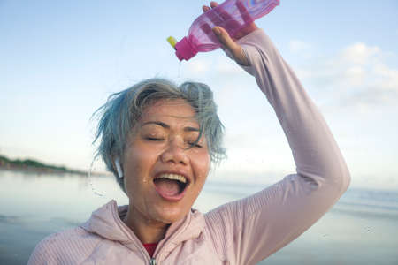Foto de happy tired and thirsty middle aged woman drinking water after beach running workout - 40s or 50s attractive mature lady with grey hair re hydrating  exhausted after jogging - Imagen libre de derechos