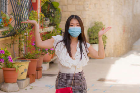 Photo pour new normal tourism and travel - young happy and beautiful Asian Japanese woman in face mask visiting Seville in Spain enjoying Europe Summer holiday relaxed during city tour - image libre de droit