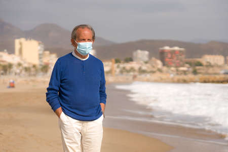 Photo pour Senior pensioner taking a walk relaxed on the beach - retired old man on his 70s looking at the sea thoughtful and contemplative with surgical mask on his hand in health concept - image libre de droit