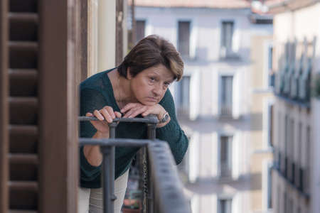 Photo pour dramatic lifestyle portrait of mature woman on her 70s depressed and sad at home balcony feeling desperate suffering anxiety problem in senior female depression concept - image libre de droit