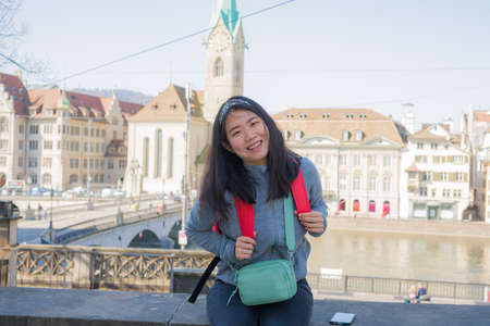 Photo pour Asian woman backpacker touring in Europe - young happy and pretty Korean girl with backpack having city and river view from bridge during holidays in Europe - image libre de droit