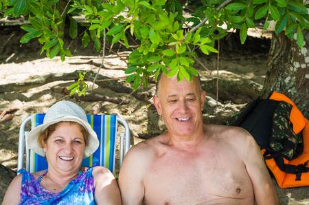 Foto de Old couple laughing on the beach, sitting, love. - Imagen libre de derechos