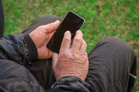 Foto de Close up of a wrinkled finger touching the smartphone, old man uses technology. Internet. - Imagen libre de derechos