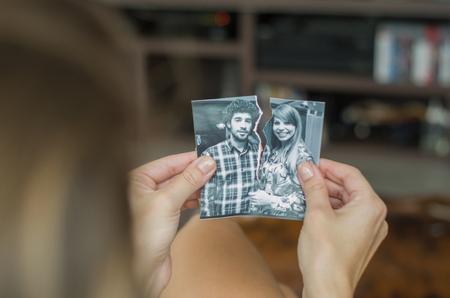 Foto de Great concept of divorce, betrayal, separation, woman hand ripping photo of the couple. - Imagen libre de derechos