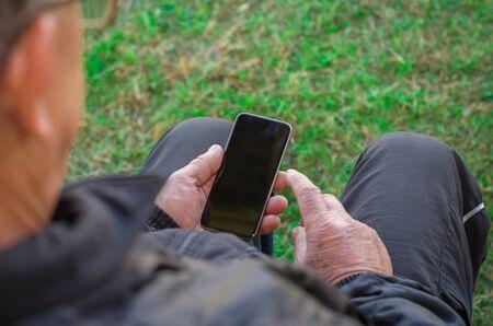 Foto de Close up of a man's wrinkled finger touching a cell phone - Imagen libre de derechos