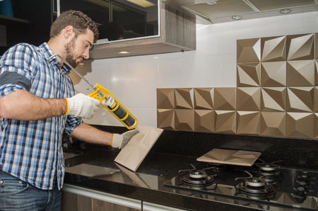 Foto de Man renovating, renovating the kitchen, installing tile on the wall. - Imagen libre de derechos