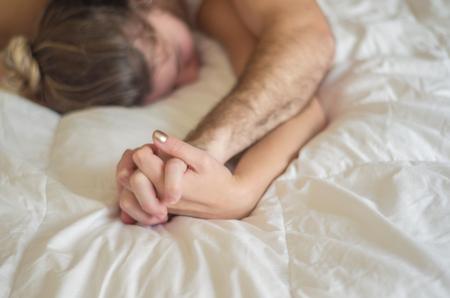 Foto de Young couple making love in bed focus on hand - Imagen libre de derechos