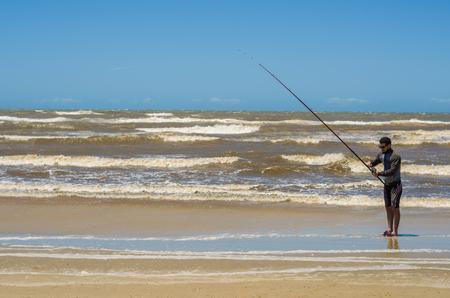 Foto de Young man fishing on beach, sport fishing. - Imagen libre de derechos