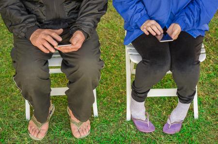 Foto de Close-up of senior couple sitting, using smartphone, cellphone, technology. - Imagen libre de derechos