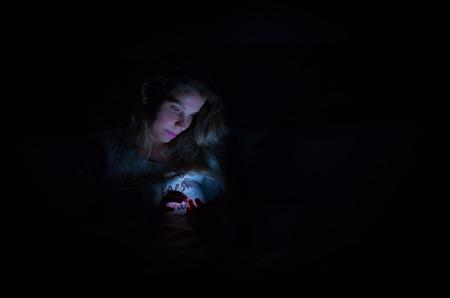 Foto de Great concept of interactivity by social media using smartphone, woman using smartphone at night in bed, portrait in low key, black background, low light. Color image. - Imagen libre de derechos