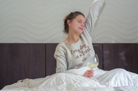 Foto de Young blonde woman stretching on bed with glass of wine in hand, waking up happy. - Imagen libre de derechos