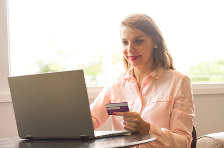 Foto de Young blond caucasian woman shopping on the internet, credit card in hand. - Imagen libre de derechos