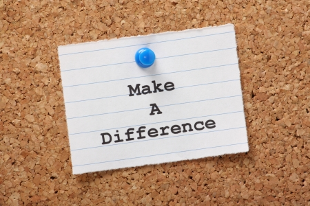 The phrase Make A Difference on a paper note pinned to a cork notice board