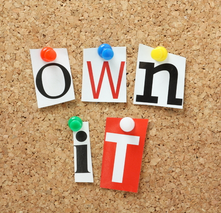 Photo pour The phrase Own It in cut out magazine letters pinned to a cork notice board - image libre de droit