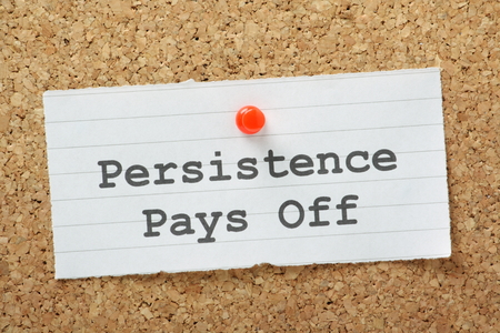 The phrase Persistence Pays Off typed on a paper note and pinned to a cork notice board
