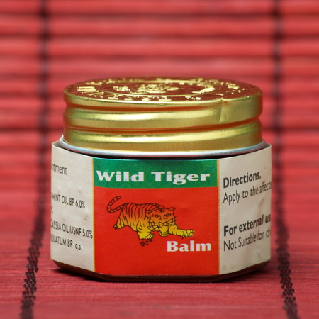 London, England - October 1st, 2014: A jar of Wild Tiger Balm red ointment, a topical analgesic made from herbal ingredients. It is estimated that 20 million jars are sold every year in 70 countries.