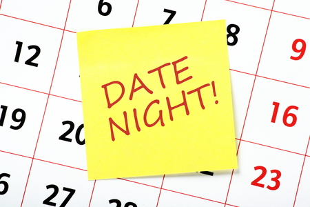 The phrase Date Night on a yellow sticky note attached to a calendar as a reminder of a special event