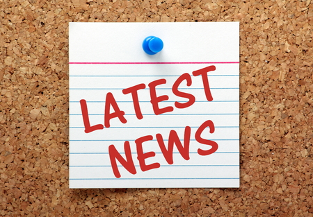 The phrase Latest News on a lined index card pinned to a cork bulletin board