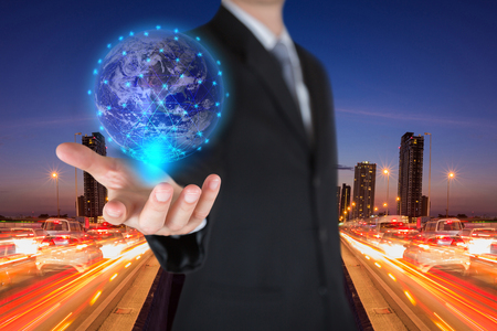 Photo pour Businessman holding the glowing hologram digital globe on light trails street, urban in the night as business, innovation, intelligent and idea concept. Elements of this image furnished by NASA - image libre de droit
