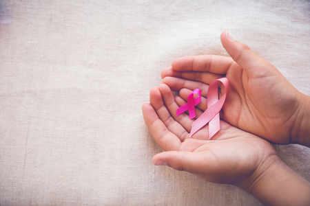 Foto per Hands holding Pink Ribbons toning background, Breast cancer awareness and Abdominal cancer awareness - Immagine Royalty Free