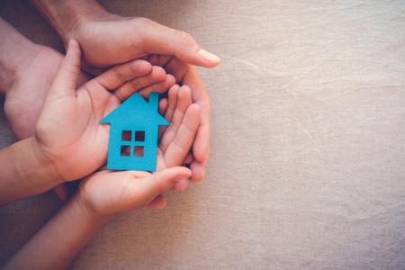 Foto de Adult and child hands holding paper house, family home and real estate concept - Imagen libre de derechos