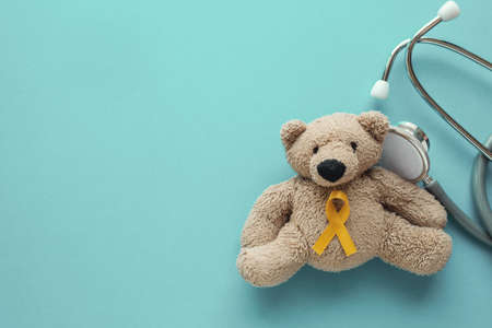 Photo pour Children soft toy brown bear with yellow gold ribbon and stethoscope, Childhood cancer awareness - image libre de droit