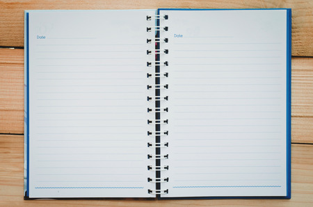 Photo for empty notebook paper and blue line with copy space open on wood table. - Royalty Free Image