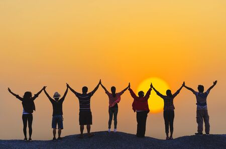 Photo pour teamwork concept silhouette diversity people show hands high up over head successful partner together at sunset on top rock hill. - image libre de droit
