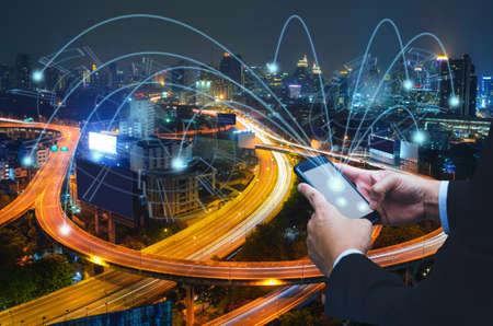 Photo pour Businessman using touching button on mobile phone and link money point to city - image libre de droit