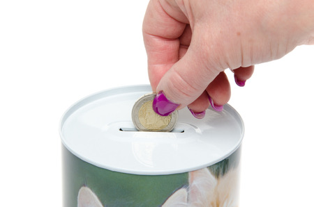 Woman's hand putting a coin in a moneybox, isolated on white