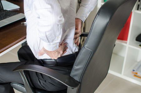 Businessman with back pain at office