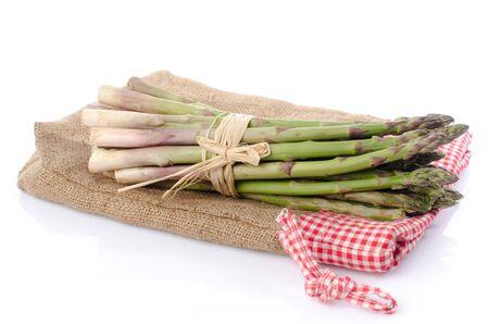 Photo pour Bunch of fresh asparagus on a burlap bag, isolated on white - image libre de droit