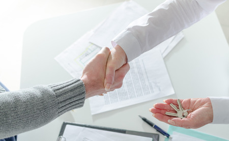 Photo for Realtor shaking hands with his client after handing over the keys - Royalty Free Image