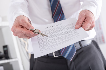 Photo pour Real estate agent giving house keys with contract (random english dummy text used) - image libre de droit