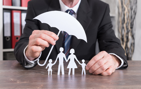 Family protected with an umbrella by an insurer - insurance conceptの写真素材