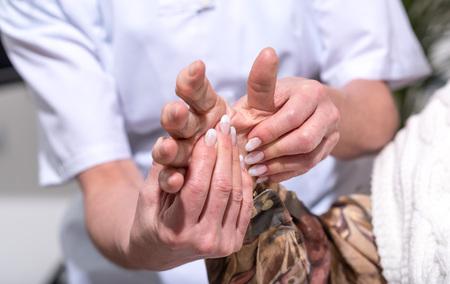 Nurse massaging the hand of a senior woman