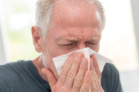 Senior man blowing his nose