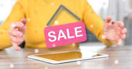 Photo pour Digital tablet with sale concept between hands of a woman in background - image libre de droit