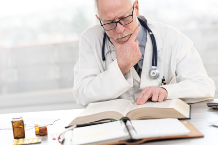 Foto de Senior doctor reading a textbook in medical office - Imagen libre de derechos