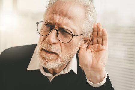 Foto de Portrait of senior man having hearing problems - Imagen libre de derechos
