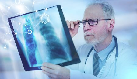 Photo pour Senior doctor looking at x-ray in clinic; multiple exposure - image libre de droit